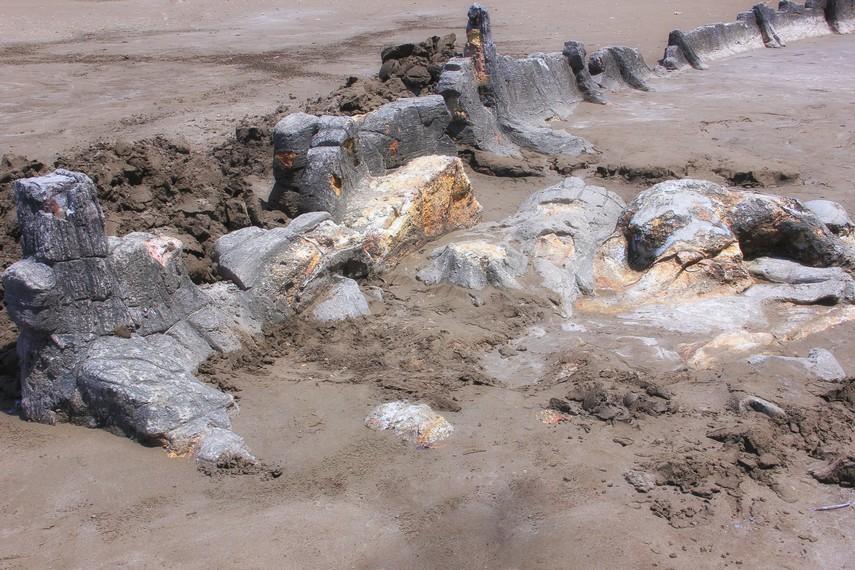 Batu Malin Kundang dikelilingi oleh gundukan batu berbentuk lambung kapal, tambang dan gentong