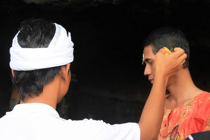 Petugas memasangkan kembang di telinga pengunjung untuk menyempurnakan ritual pemberkatan