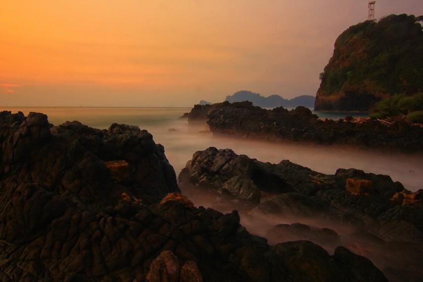 Siluet tebing yang menjulang tinggi menjadi hiasan indah pada sisi kanan pantai ini