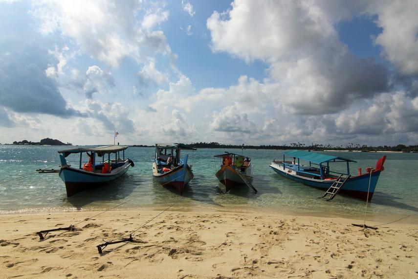 Perahu-perahu yang mengantarkan pengunjung ke Pulau Pasir bersandar di tepi pulau