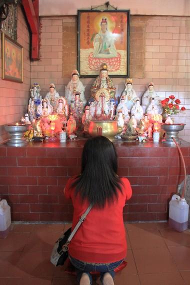 Seorang pengunjung sedang sembahyang di salah satu tempat sembahyang yang ada di vihara ini