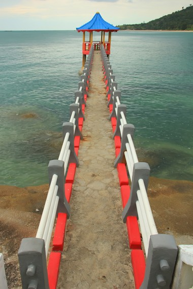 Jembatan yag menjorok ke laut menjadi salah satu pemandangan yang dapat disaksikan di Pantai Tanjung Pesona