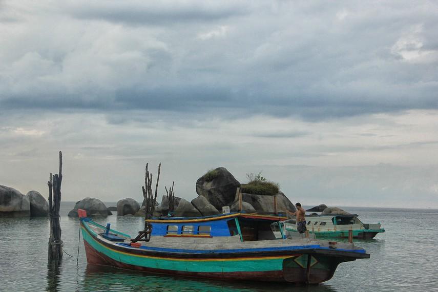 Perahu nelayan dan batu granit menjadi dekorasi cantik yang ada di Pantai Teluk Limau