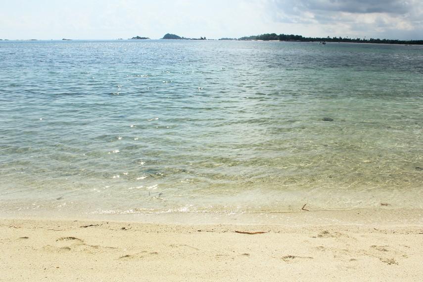 Air laut yang jernih dan ombak yang tenang membuat bermain air di pulau ini terasa menyenangkan