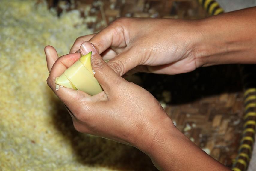 Proses pengisian ketan kedalam daun kelapa untuk kemudian direbus