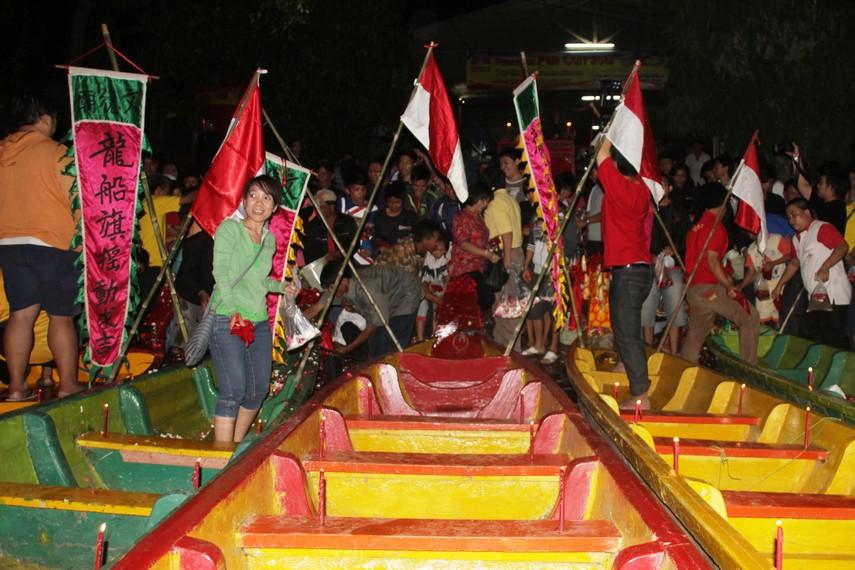 Masyarakat juga turut memandikan perahu naga yang keesokan harinya akan digunakan untuk lomba perahu naga