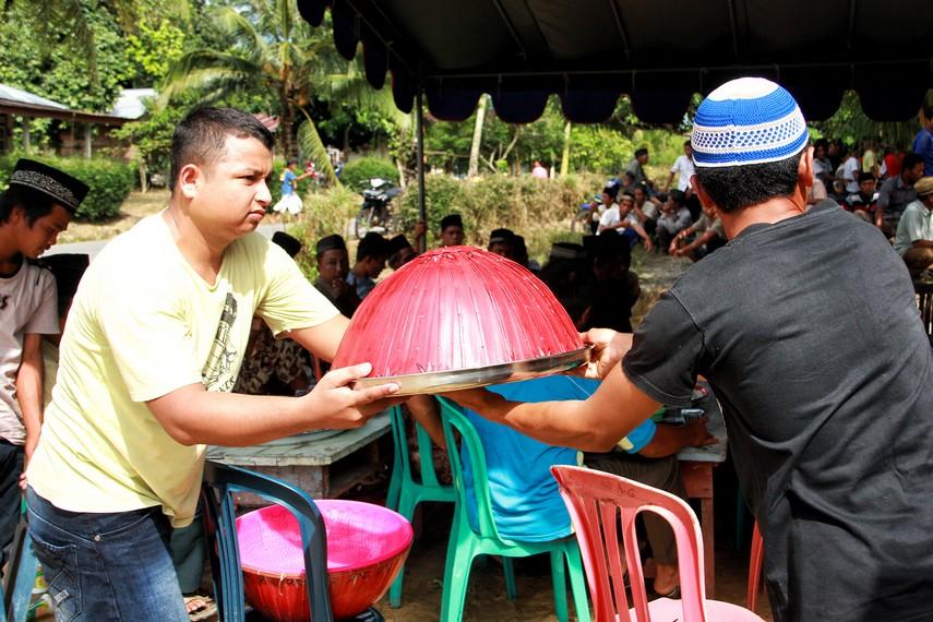 Warga saling membagi-bagikan makanan yang akan dimakan bersama-sama seluruh warga kampung