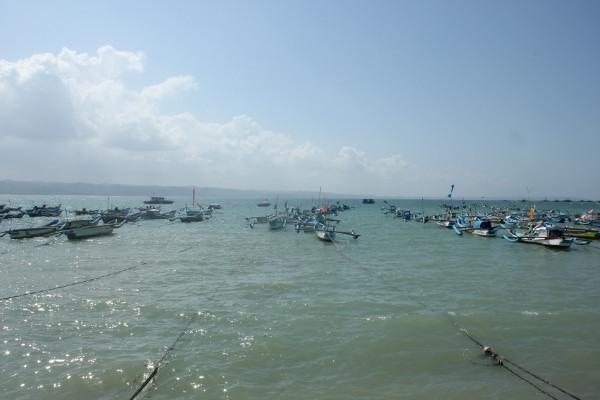 Aneka perahu nelayan yang diikat di tepi Pantai Pangandaran di siang hari