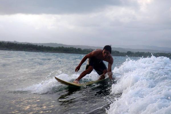 Salah satu peselancar melakukan manuver di atas ombak Pantai Batu Karas