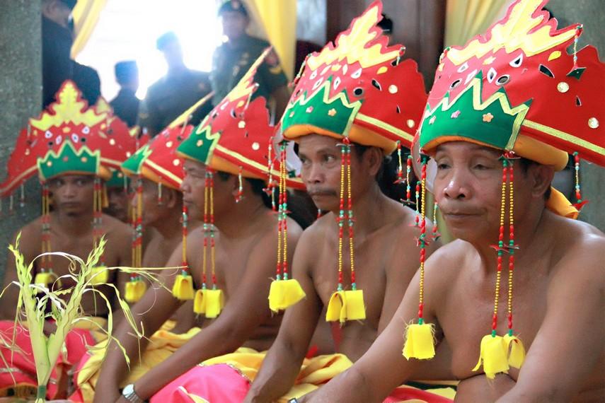 Para Belian (pria pengabdi ritual) duduk berjajar di samping Tiang Ayu