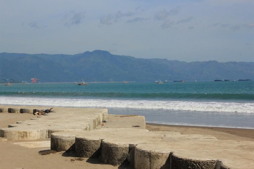 Pemandangan bukit dan kapal-kapal nelayan menjadi paduan yang menarik pandangan mata saat berada di pantai ini