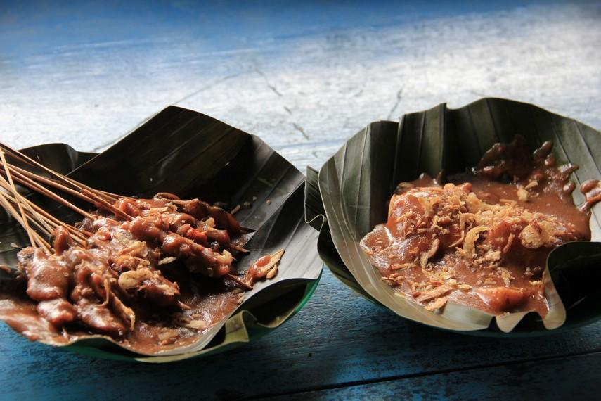 Seporsi lengkap sate lokan disajikan bersama potongan ketupat, lengkap dengan taburan bawang goreng yang nikmat