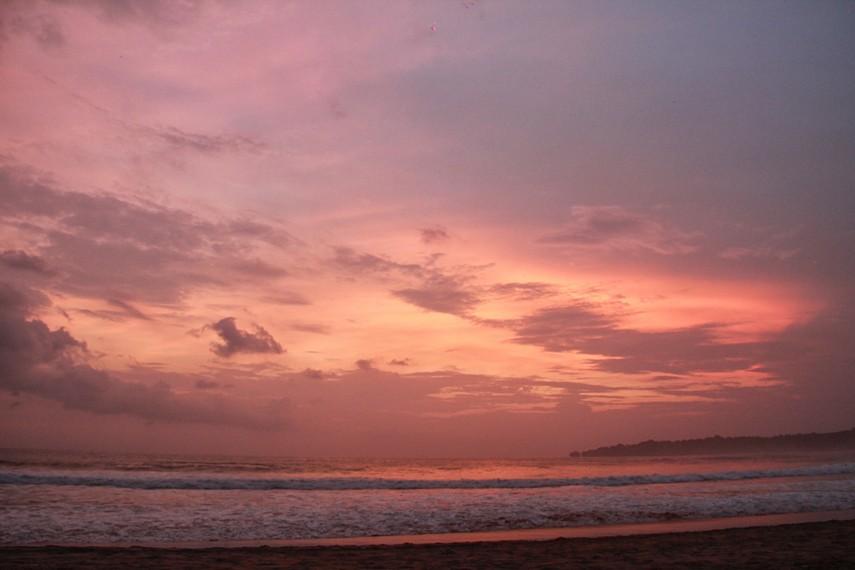 Pemandangan langit senja yang memerah di Pantai Pasir Putih Sawarna menjadi sajian indah di sini