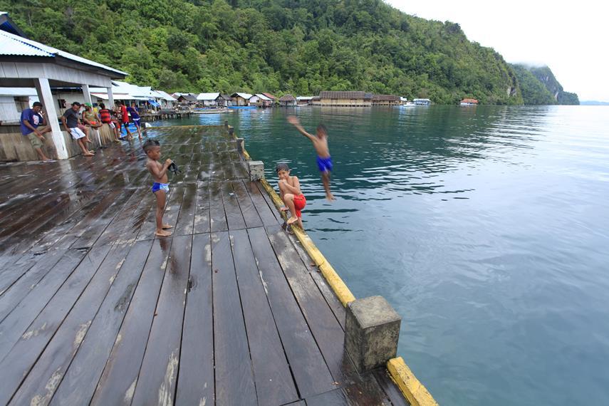 Anak-anak Desa Sawai yang sangat atraktif berenang di pinggir dermaga Sawai