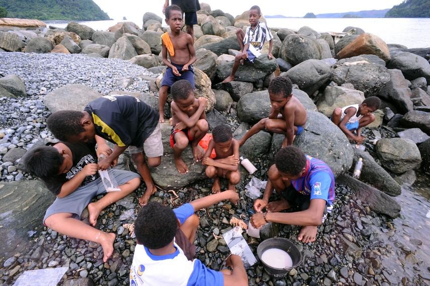 Anak-anak Desa Tablanusu asyik bermain sambil menangkap ikan di pinggir pantai