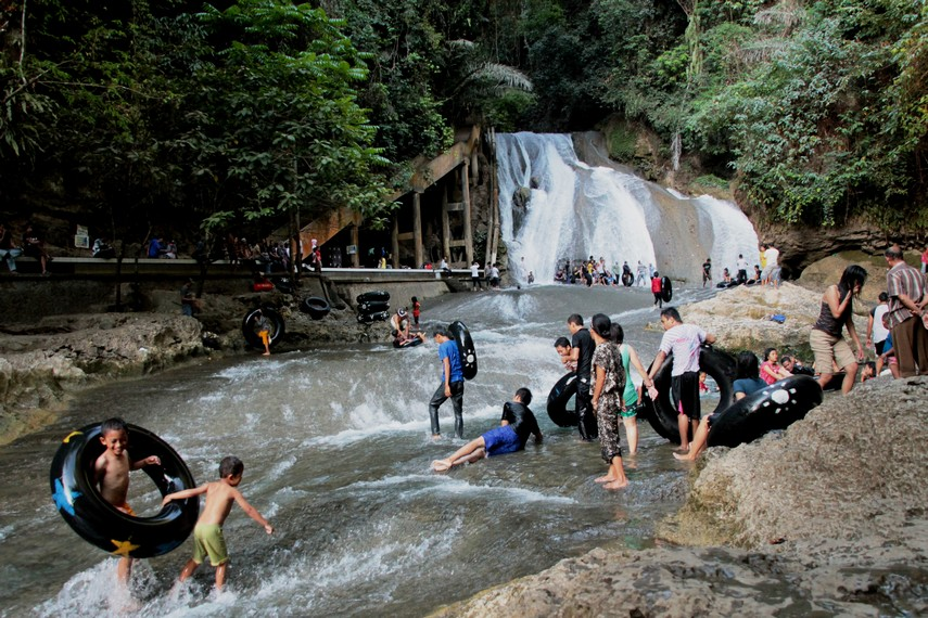 Para pengunjung sedang asyik bermain air di Taman Bantimurung