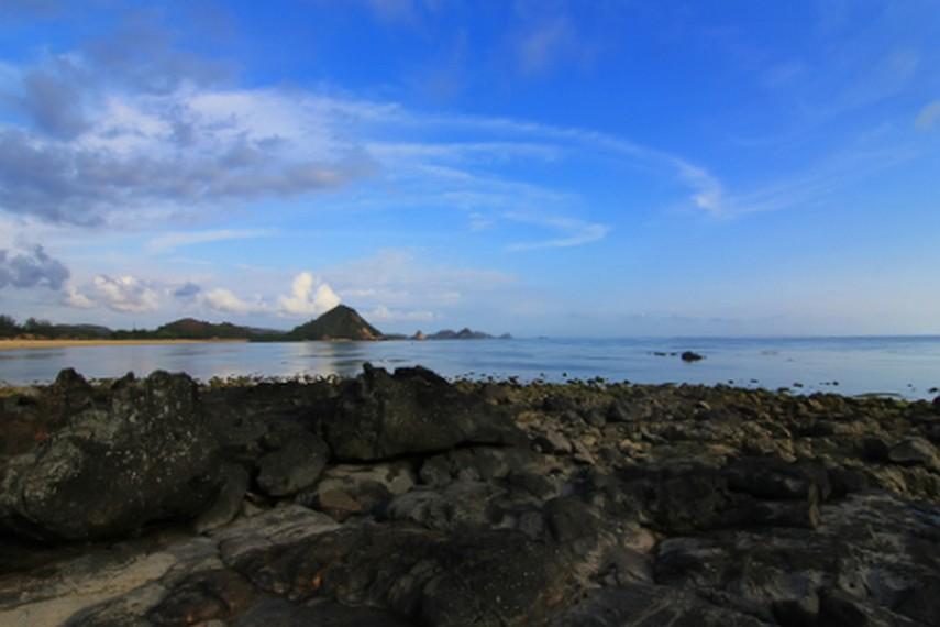 Bebatuan karang menjadi pemandangan lain yang disajikan Pantai Kuta saat air surut