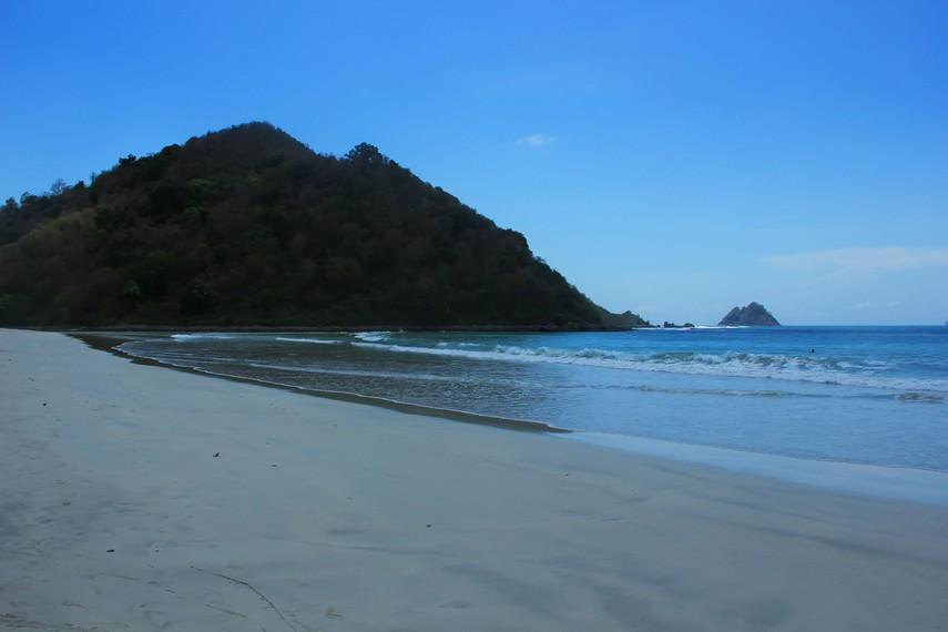 Bukit hijau di sudut pantai menambah keindahan Pantai Selong Belanak
