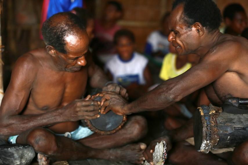 Dua orang bapak sedang mengencangkan kulit biawak yang menjadi selaput untuk tifa