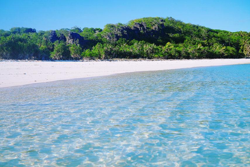 Hamparan pasir putih dengan latar belakang bukit hijau nan asri