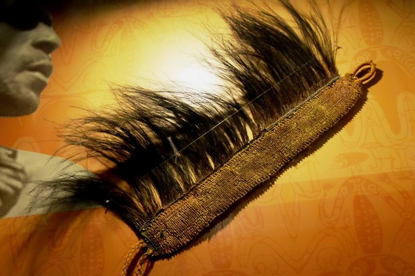 Hiasan kepala Suku Asmat yang terbuat dari daun sagu, bagian atasnya dilengkapi bulu burung kasuari. Hiasan ini biasa digunakan oleh kaum laki-laki