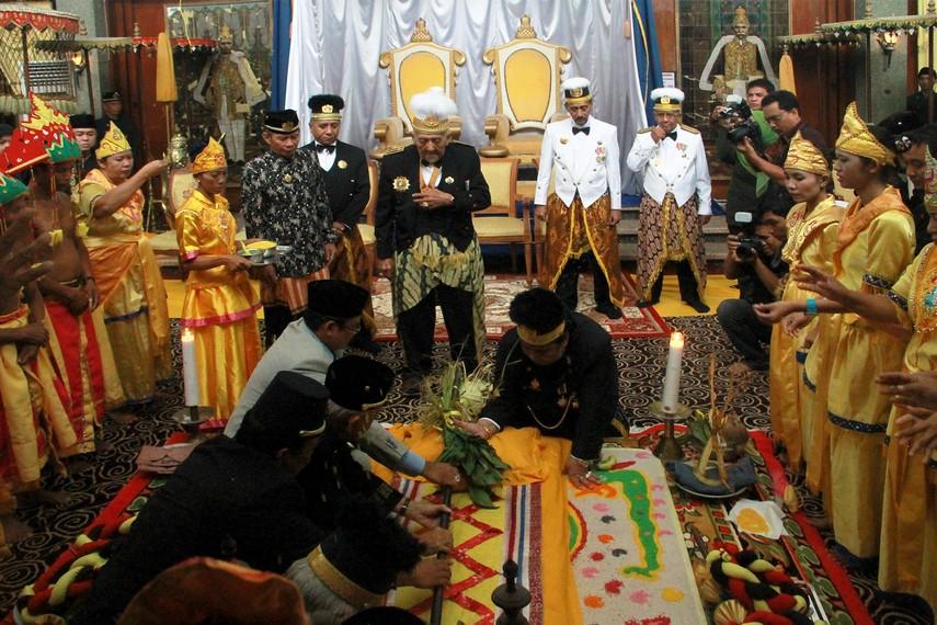Empat orang kerabat keraton berjajar di sisi Sangkoh Piatu dan merebahkannya ke atas kasur dengan disaksikan Sultan