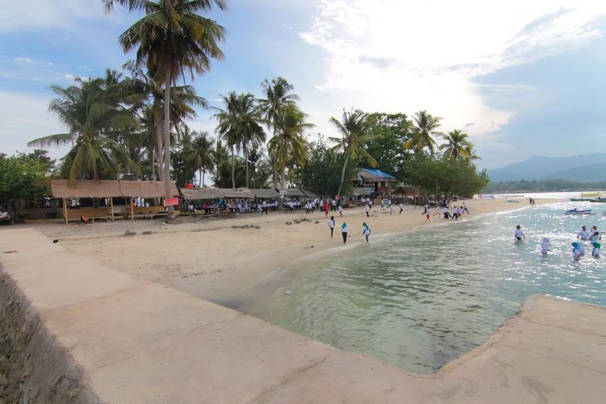 Suasana wisatawan menikmati kesenangan bermain air di Pantai Mutun