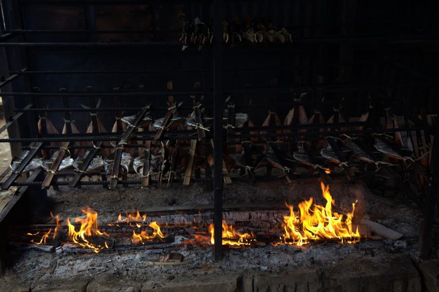 Ikan diletakkan di atas api dan akan matang oleh asap