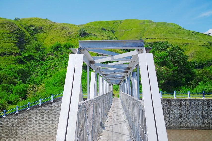 Jembatan besi yang membentang  cukup panjang di atas aliran bendungan ini, menghubungkan kedua desa