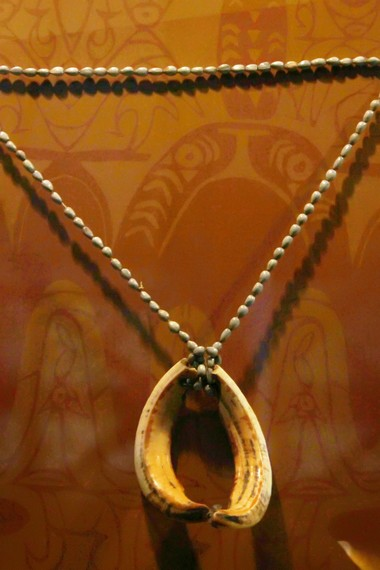 Kalung Suku Asmat yang terbuat dari kerang dan taring babi. Kalung ini biasa dipakai oleh laki-laki maupun perempuan