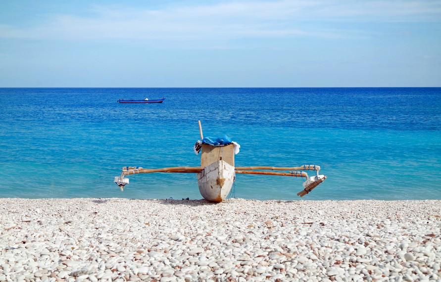 Panorama birunya air laut dan hamparan bebatuan krikil yang berwarna-warni