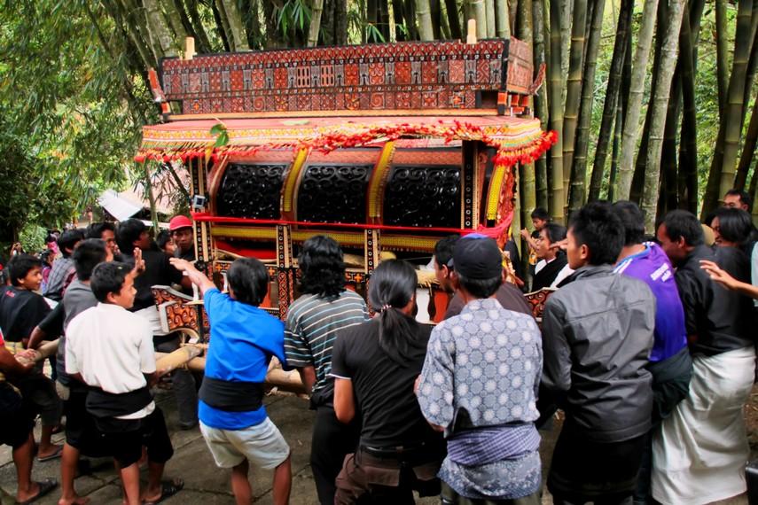 Para kerabat dibantu warga sekitar bahu membahu membawa peti jenazah yang sudah diberkati
