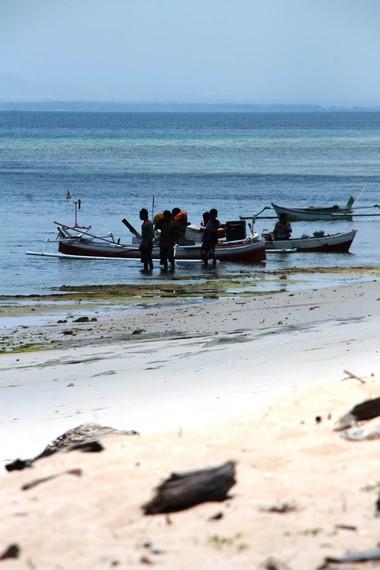 Para nelayan menyandarkan perahu di Pantai Lemo-Lemo sehabis melaut