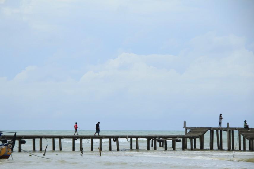 Pengunjung menikmati suasana laut diatas jembatan di Pantai Bandengan