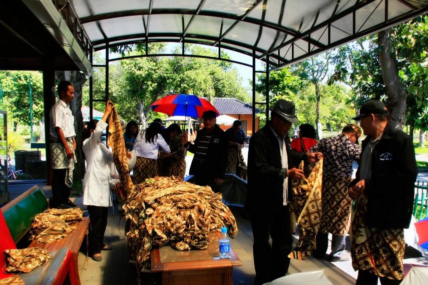 Pengunjung sedang mengenakan batik sebelum masuk Candi Borobudur
