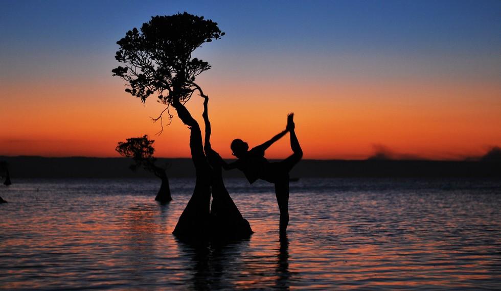 Perpaduan artistik antara langit senja dan siluet yoga ketika matahari terbenam di Walakiri