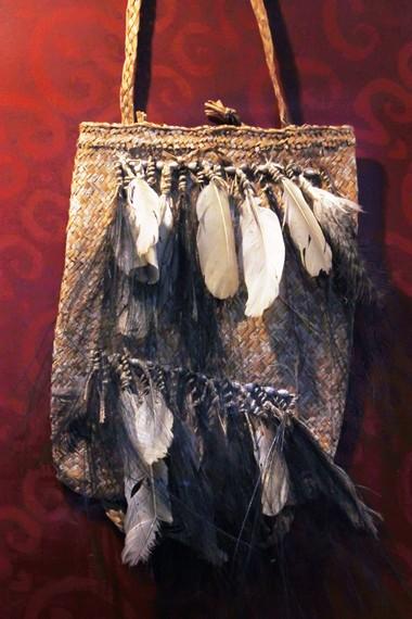 Salah satu tas hasil produksi Suku Asmat, terbuat dari daun sagu dan dilengkapi hiasan dari kerang dan bulu burung