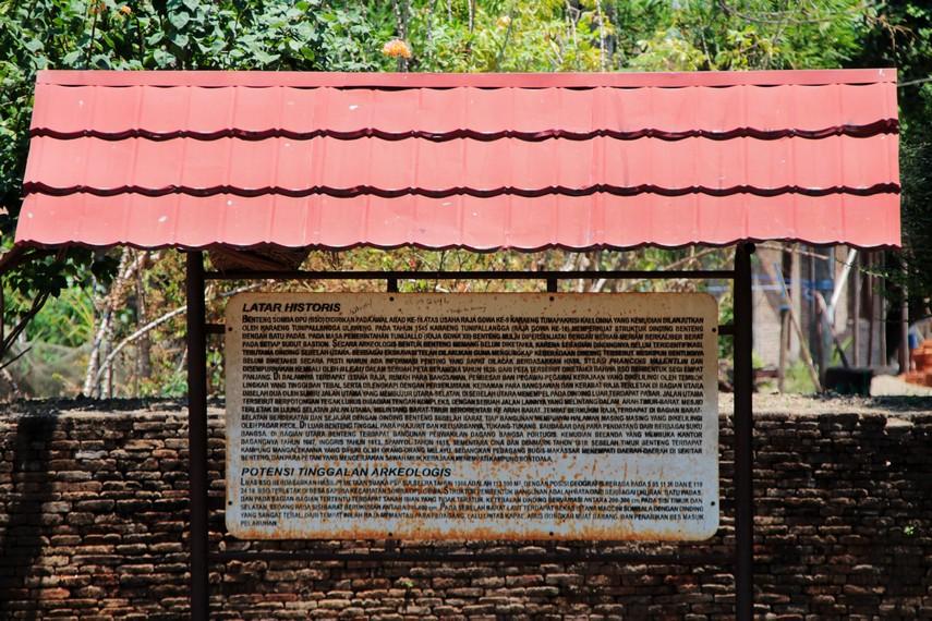 Sebuah papan penjelasan yang menceritakan latar historis Benteng Somba Opu beserta potensi peninggalan arkeologisnya
