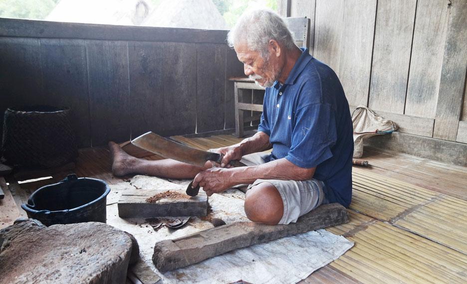 Seorang bapak sedang membuat kerajinan tangan dari batok kelapa