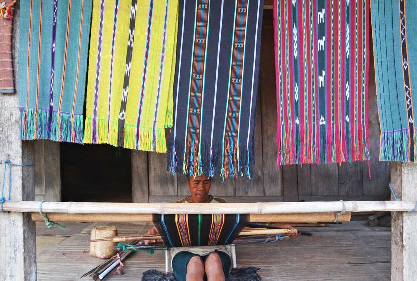Seorang ibu sedang membuat kain tenun khas Bena
