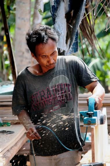Seorang pekerja yang sedang menghaluskan kayu yang menjadi bahan utama pembuatan perahu Pinisi