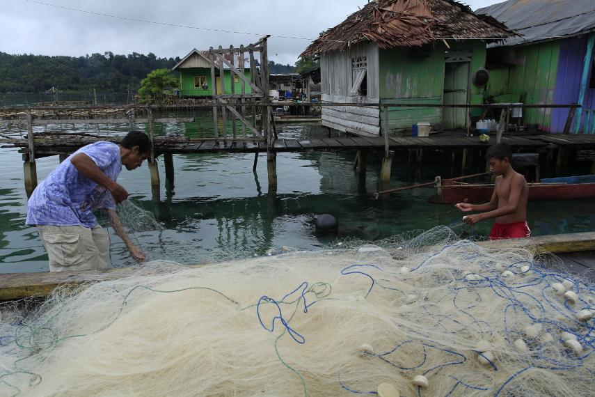 Seorang anak yang sedang membantu ayahnya merapikan jaring ikan