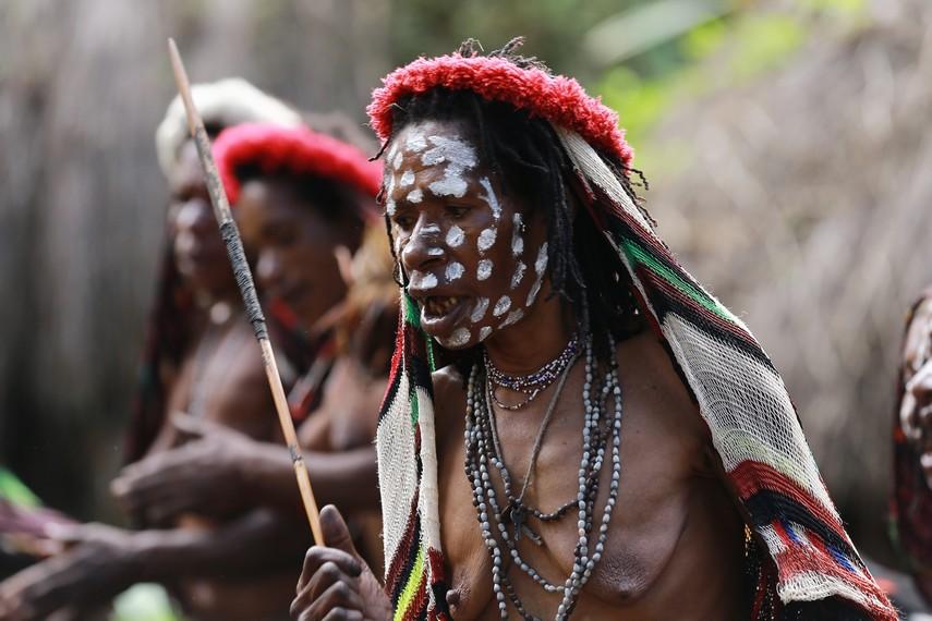 Seorang wanita yang dituakan di desa mulai memimpin nyanyian selamat datang mereka