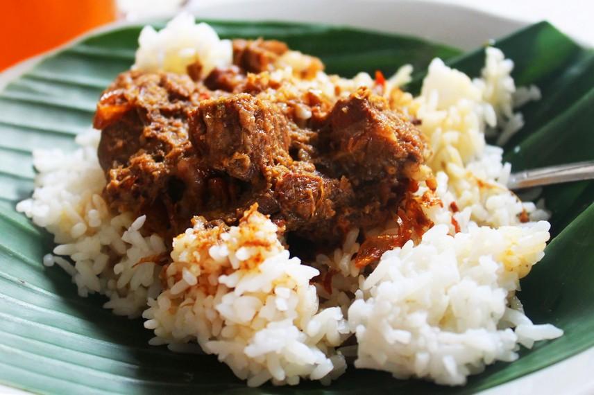 Sepiring nasi putih yang disajikan dengan potongan daging sapi yang empuk dan disiram dengan kuah kental