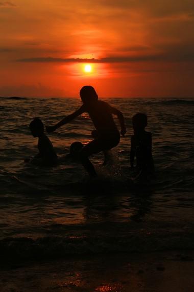 Suasana anak-anak bermain di pantai saat menjelang matahari terbenam