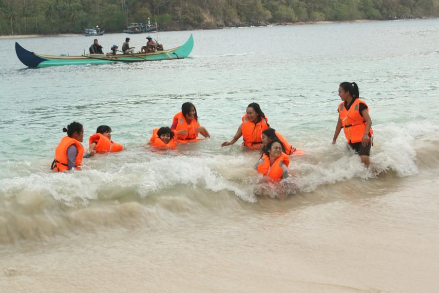 Suasana pengunjung yang menikmati bermain air di pinggir pantai Pulau Kiluan