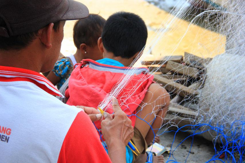 Melihat aktivitas para nelayan yang sedang membuat jala menjadi salah satu sajian di Pantai Kenjeran