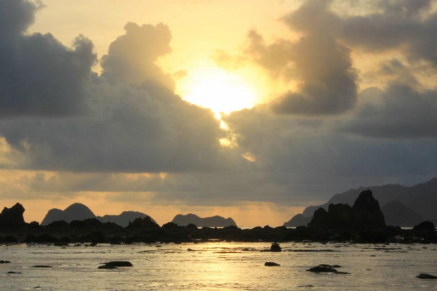 Saat senja, pemandangan matahari tenggelam menjadi sajian indah bagi para pengunjung Pantai Pulau Merah