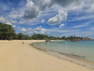 Duduk Menikmati Matahari Terbenam di Pantai Tanjung Tinggi