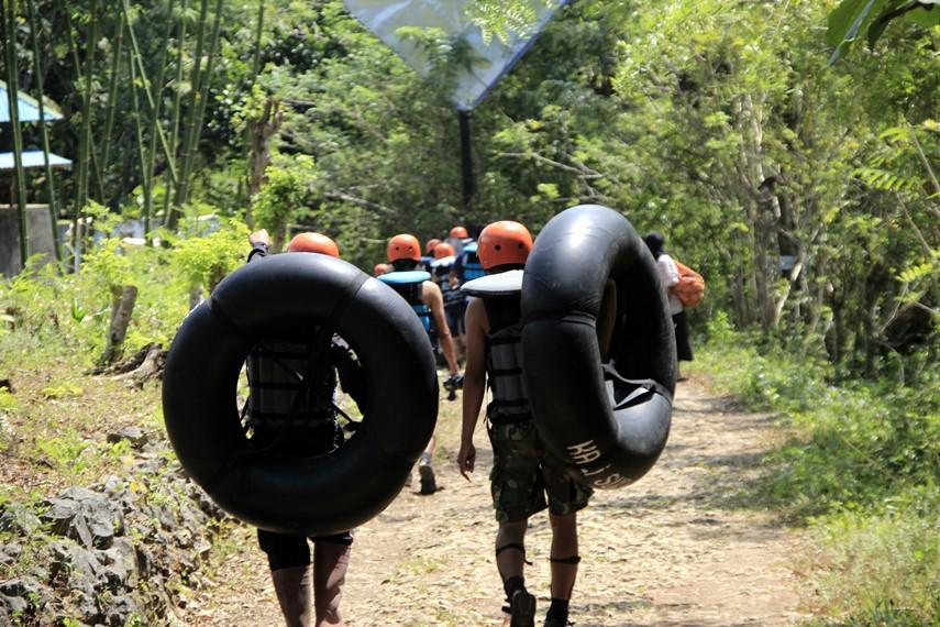 Para pengunjung membawa ban yang akan digunakan selama mereka menyusuri gua